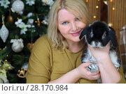 Купить «Blonde woman sits and holds bunny near christmas tree in cozy room», фото № 28170984, снято 20 ноября 2015 г. (c) Losevsky Pavel / Фотобанк Лори