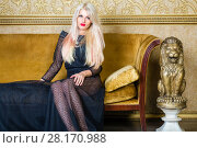 Купить «Pretty blonde in black lace dress sits on couch with yellow upholstery in roo», фото № 28170988, снято 20 ноября 2015 г. (c) Losevsky Pavel / Фотобанк Лори