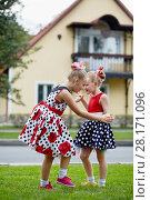 Купить «Two girls in polka-dotted dresses dance on grassy lawn against two-storied house», фото № 28171096, снято 10 сентября 2016 г. (c) Losevsky Pavel / Фотобанк Лори