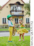 Купить «Little boy in dancing suit plays saxophone and little girl dances on grassy lawn against two-storied house», фото № 28171112, снято 10 сентября 2016 г. (c) Losevsky Pavel / Фотобанк Лори