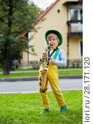 Купить «Little boy in dancing suit plays saxophone on grassy lawn against two-storied house», фото № 28171120, снято 10 сентября 2016 г. (c) Losevsky Pavel / Фотобанк Лори