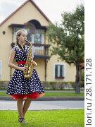 Купить «Teenage girl plays saxophone on grassy lawn near road against two-storied house», фото № 28171128, снято 10 сентября 2016 г. (c) Losevsky Pavel / Фотобанк Лори