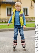 Купить «Boy on roller skates in front of house on street», фото № 28171172, снято 10 сентября 2016 г. (c) Losevsky Pavel / Фотобанк Лори