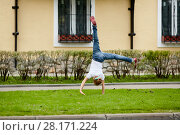 Купить «Girl turns cartwheel on grassy lawn in front of house», фото № 28171224, снято 10 сентября 2016 г. (c) Losevsky Pavel / Фотобанк Лори