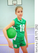 Купить «Pretty girl in green stands with volleyball in gym with basketball ring out of focus», фото № 28171292, снято 11 сентября 2016 г. (c) Losevsky Pavel / Фотобанк Лори