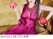 Купить «Young woman sits on couch, holding pomegranates in hands», фото № 28171408, снято 9 декабря 2015 г. (c) Losevsky Pavel / Фотобанк Лори