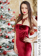 Купить «Young girl in red dress stands in room decorated to christmas holidays», фото № 28171456, снято 9 декабря 2015 г. (c) Losevsky Pavel / Фотобанк Лори