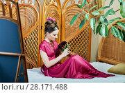 Купить «Young woman with bunch of flowers sits on wicker bed», фото № 28171488, снято 9 декабря 2015 г. (c) Losevsky Pavel / Фотобанк Лори