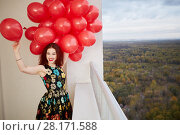 Купить «Young smiling red-haired woman holds in hand bunch of red balloons standing at balcony of highrise building», фото № 28171588, снято 15 октября 2015 г. (c) Losevsky Pavel / Фотобанк Лори