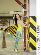 Купить «Young smiling woman does stretching exercise  leaning on column in underground parking», фото № 28171608, снято 15 октября 2015 г. (c) Losevsky Pavel / Фотобанк Лори