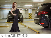 Купить «Young red-haired woman in black dress poses at underground parking among cars», фото № 28171616, снято 15 октября 2015 г. (c) Losevsky Pavel / Фотобанк Лори