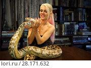Купить «Pretty blonde woman holds big snake and smiles indoor, snake lies on table», фото № 28171632, снято 18 июля 2016 г. (c) Losevsky Pavel / Фотобанк Лори