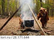 MOSCOW - OCT 18, 2015: Chukchi in their national costumes near fire in ethno-cultural complex Husky Park in Sokolniki. Редакционное фото, фотограф Losevsky Pavel / Фотобанк Лори
