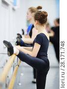 Купить «Girl in black leotard stretch in ballet class, other girls out of focus», фото № 28171748, снято 25 апреля 2016 г. (c) Losevsky Pavel / Фотобанк Лори