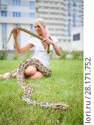 Купить «Pretty woman with two snakes on green lawn near building, focus on snake», фото № 28171752, снято 18 июля 2016 г. (c) Losevsky Pavel / Фотобанк Лори