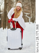 Купить «Young woman with white trolley bag stands in winter park», фото № 28171968, снято 15 января 2016 г. (c) Losevsky Pavel / Фотобанк Лори