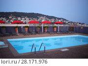 Купить «Empty small pool on rooftop, loungers, umbrellas at evening in town on mountain», фото № 28171976, снято 24 июля 2016 г. (c) Losevsky Pavel / Фотобанк Лори