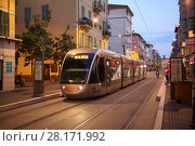Купить «NICE, FRANCE - JUL 25, 2016: Tram travels along city street at evening. Tram system in Nice restored in 2007», фото № 28171992, снято 25 июля 2016 г. (c) Losevsky Pavel / Фотобанк Лори
