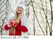 Купить «Young smiling woman stands making snowball in winter park», фото № 28171996, снято 15 января 2016 г. (c) Losevsky Pavel / Фотобанк Лори