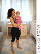 Купить «Young mother with curly hair in sportswear holding a baby in front of a window in the room», фото № 28172188, снято 4 октября 2016 г. (c) Losevsky Pavel / Фотобанк Лори