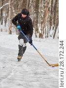 Купить «Hockey player carries puck at outdoor skating rink in park», фото № 28172244, снято 21 января 2016 г. (c) Losevsky Pavel / Фотобанк Лори
