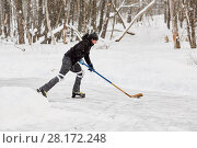 Купить «Hockey player carries puck at outdoor skating rink in park», фото № 28172248, снято 21 января 2016 г. (c) Losevsky Pavel / Фотобанк Лори