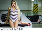 Купить «Young blonde woman in striped bodysuit poses sitting on modern white car trunk at underground parking», фото № 28172320, снято 2 июня 2016 г. (c) Losevsky Pavel / Фотобанк Лори