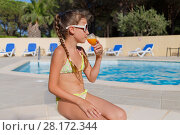 Купить «Girl in bikini with glass of orange juice in hand sitting in swimming pool in hotel courtyard», фото № 28172344, снято 1 августа 2016 г. (c) Losevsky Pavel / Фотобанк Лори