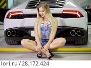 Купить «Young woman in striped bodysuit, jeans overall and high-heel shoes sits on yellow pipe at back of modern white car at underground parking», фото № 28172424, снято 2 июня 2016 г. (c) Losevsky Pavel / Фотобанк Лори
