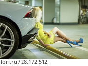 Купить «Young woman in yellow dress sits on yellow pipe leaning back onto trunk of modern white car at underground parking», фото № 28172512, снято 2 июня 2016 г. (c) Losevsky Pavel / Фотобанк Лори
