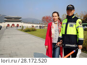 Купить «SEOUL - NOV 2, 2015: Woman (with model release) poses with policemen near gate to palace Gyeongbokgung with pagoda. Gate to royal palace of Gyeongbokgung is important symbol of Korea», фото № 28172520, снято 2 ноября 2015 г. (c) Losevsky Pavel / Фотобанк Лори