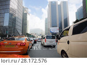 Купить «SEOUL - NOV 3, 2015: Taxi and other cars driving on street near buildings. In Seoul pledged to limit advertising of cosmetic surgery», фото № 28172576, снято 3 ноября 2015 г. (c) Losevsky Pavel / Фотобанк Лори