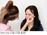 Купить «makeup artist paints eyebrows for young girl», фото № 28178424, снято 14 марта 2018 г. (c) Володина Ольга / Фотобанк Лори