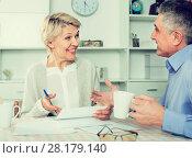 positive mature couple at table attentively study documents. Стоковое фото, фотограф Яков Филимонов / Фотобанк Лори