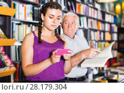 Купить «Mature male is choosing book while young girl surfing in phone», фото № 28179304, снято 28 июня 2017 г. (c) Яков Филимонов / Фотобанк Лори