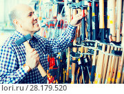 Купить «Pensioner selecting nails and hummer», фото № 28179520, снято 19 ноября 2018 г. (c) Яков Филимонов / Фотобанк Лори