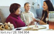 Купить «Grandmother with daughter and granddaughter enjoying conversation on sofa at home», видеоролик № 28184904, снято 27 ноября 2017 г. (c) Яков Филимонов / Фотобанк Лори