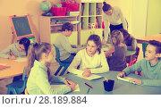 Купить «Portrait of young teacher woman at lesson with diligent school kids», фото № 28189884, снято 28 января 2018 г. (c) Яков Филимонов / Фотобанк Лори