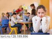 Купить «Upset girl in schoolroom on background with pupils», фото № 28189896, снято 28 января 2018 г. (c) Яков Филимонов / Фотобанк Лори