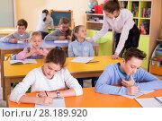 Купить «Portrait of young teacher woman at lesson with diligent school kids», фото № 28189920, снято 28 января 2018 г. (c) Яков Филимонов / Фотобанк Лори