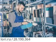 Купить «Smiling male worker looking through sanitary drain pipes», фото № 28190364, снято 15 марта 2017 г. (c) Яков Филимонов / Фотобанк Лори