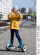 Купить «Девочка стоит на гироскутере в городе и показывает большой палец вверх», фото № 28191680, снято 17 марта 2018 г. (c) Кекяляйнен Андрей / Фотобанк Лори