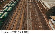 Купить «Railway yard with a lot of railway lines and freight trains. Aerial», видеоролик № 28191884, снято 22 февраля 2018 г. (c) Ярослав Ковальчук / Фотобанк Лори