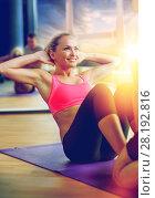 Купить «smiling woman with male trainer exercising in gym», фото № 28192816, снято 29 июня 2014 г. (c) Syda Productions / Фотобанк Лори