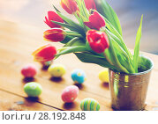 Купить «tulip flowers in bucket and easter eggs on table», фото № 28192848, снято 28 января 2016 г. (c) Syda Productions / Фотобанк Лори