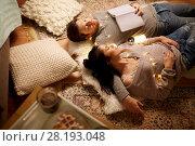 Купить «happy couple with garland lying on floor at home», фото № 28193048, снято 13 января 2018 г. (c) Syda Productions / Фотобанк Лори