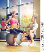 Купить «smiling man and woman with exercise ball in gym», фото № 28193148, снято 29 июня 2014 г. (c) Syda Productions / Фотобанк Лори