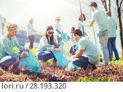 Купить «volunteers with garbage bags cleaning park area», фото № 28193320, снято 7 мая 2016 г. (c) Syda Productions / Фотобанк Лори