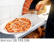 Купить «chef placing pizza from peel to plate at pizzeria», фото № 28193336, снято 17 февраля 2017 г. (c) Syda Productions / Фотобанк Лори