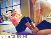 Купить «woman with personal trainer doing sit ups in gym», фото № 28193348, снято 29 июня 2014 г. (c) Syda Productions / Фотобанк Лори